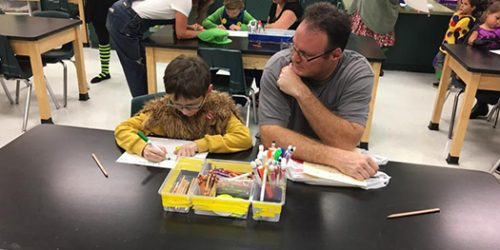 A father and son working on an art project at Spessard L Holland Elementary school.