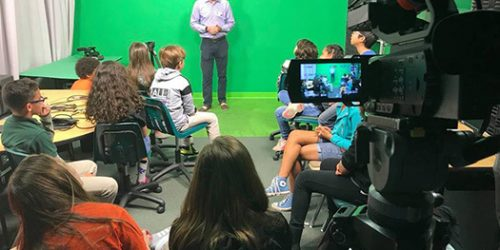 News anchor visiting school with students sitting in listening.