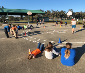 Students sitting in a large circle on blacktop at PE