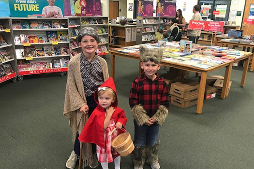 Three children dressed in costume at their school's literacy night. One is a big bad wolf, another is little red riding hood. The other student is a grandma.