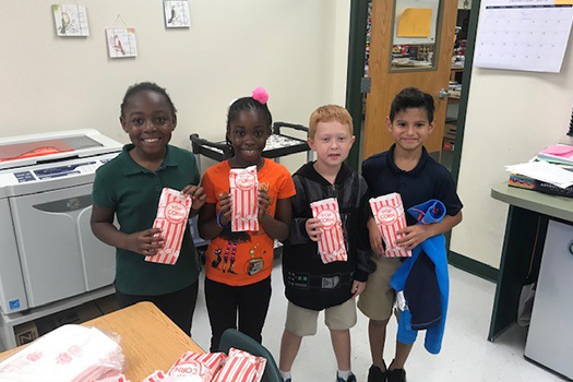 Four kids holding bags of popcorn