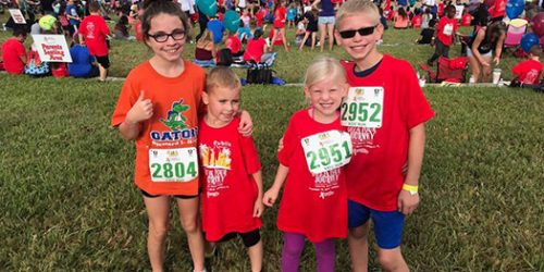 Four students standing on the lawn of lake mirror in Lakeland, Fl after they just participated in the Red Ribbon Run for kids.