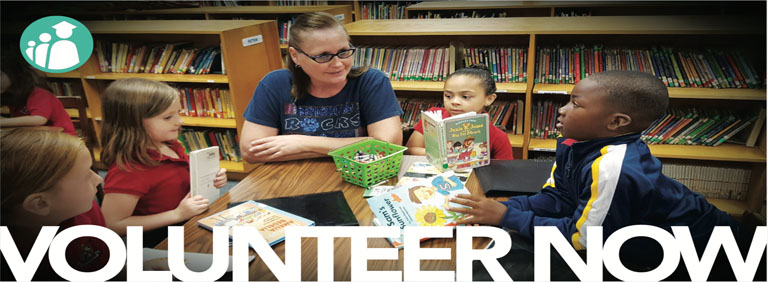 Volunteer Now Banner - Children sitting in library with teacher