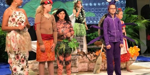 Group of elementary students in costume singing on stage