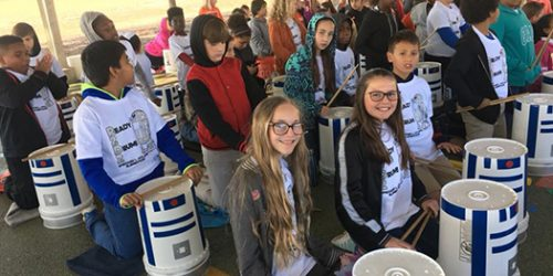Students sitting next to their drum buckets.